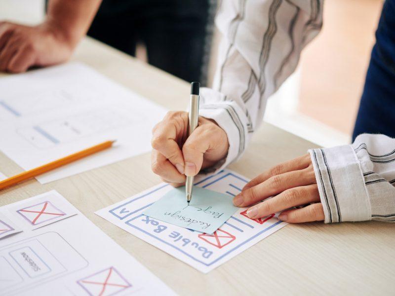 Crop woman writing on note making plan